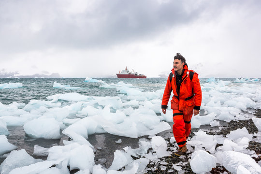Man walks through ice and snow in Antarctica. Icebergs and everything frozen around you. Cold.
