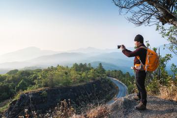 Thai Asian Man traveler take photo view mountain of doi inthanon national park with mirrorless camera