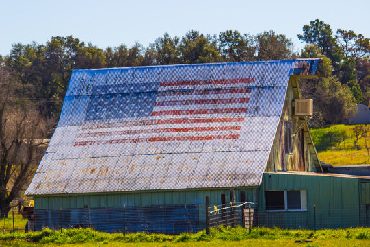 American Flag Painted On Old Tin Roof Of Barn