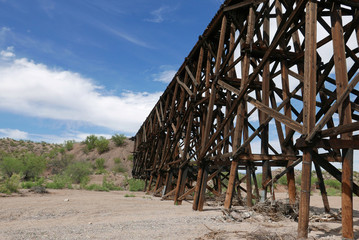 Old obsolete railroad bridge crossing dry river bed in Arizona, USA