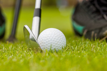 Close up of white golf ball on the golf course. There are golf clubs and golfers that are about to hit the golf ball.