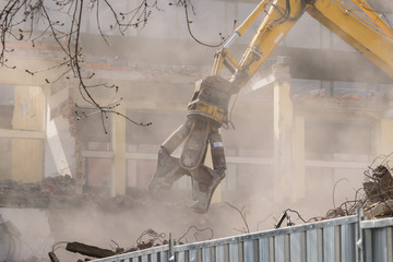 Building demolition: shears cutting through the walls - dusty