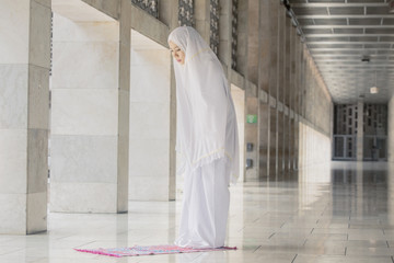 Asian Muslim woman doing Salat in the mosque
