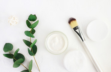 Skincare cosmetics with aroma eucalyptus plant extract. Jar of organic beauty product and application brush with fresh green leaves herbal bough, top view white background. Home spa and body care