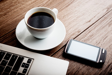 Office workplace with open laptop on wooden desk with phone and cup of coffee