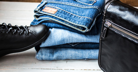 shoes and pile of jeans and bag on a wooden background