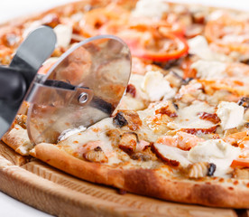 Italian kitchen and cooking concept - cook with cutter cutting pizza to pieces at pizzeria. Hot tasty sliced with salmon, eel, seafood, tomato.