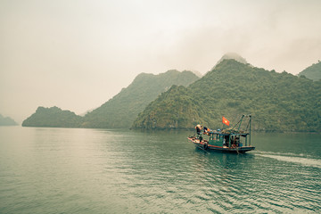 a solitary fishing boat in Ha Long Bay Vietnam