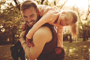 Father and daughter in meadow carrying her on shoulders.