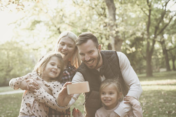 Smiling father taking self picture of family in nature.