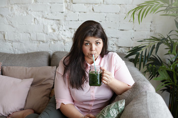 Portrait of attractive plus size young brunette woman with curvy body hoping to loose extra pounds, drinking detox fresh juice every morning, seeping green drink using straw, sitting in living room