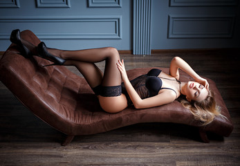 sensual woman posing in lingerie lying on couch perfect slim body