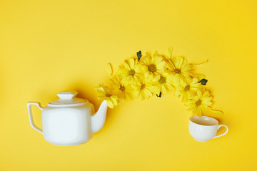 Yellow chrysanthemums pouring into cup from white pot isolated on yellow