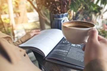 Closeup image of a woman reading book and drinking coffee in cafe