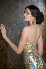 Young beautiful woman in evening gold dress