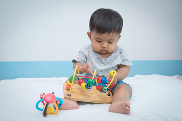 Cute little asian baby play wooden toy