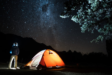 Hiker stands by the tent and enjoys night starry sky