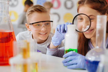 Thorough examination. Upbeat teenage girl examining a green substance in the flask with the magnifying glass while her classmate watching her do so with a smile