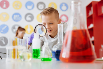 Useful tool. Cheerful handsome teenage male student using a magnifying glass and studying a chemical reaction going on in the flask