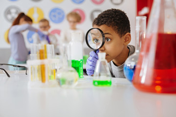 Helpful tool. Upbeat teenage boy looking at a chemical flask through a magnifying glass while examining the reaction going on in the flask