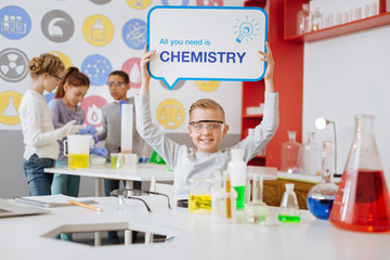 Life motto. Joyful teenage boy sitting at the table in the school chemistry lab and holding a board saying All You Need is Chemistry