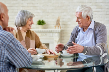 Group of senior people chatting and drinking tea enjoying time in retirement home, copy space
