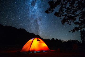 Tent and night sky. Highlighted orange hiking tent and deep starry sky with trees on the foreground.