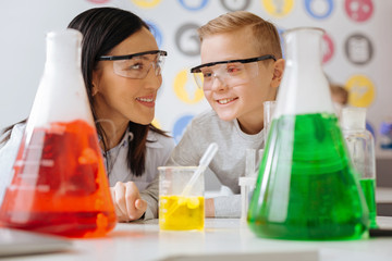Smart ideas. The close up of a pleasant upbeat chemistry teacher and her student discussing the chemical reaction while watching it going on in the flask standing on the table