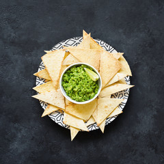 Nachos and guacamole on a plate, dark background, square crop