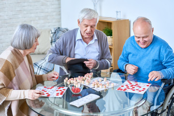 Portrait of senior people playing lotto game sitting at glass table in living room of retirement home