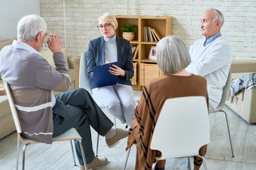 Portrait of blonde female psychiatrist leading group therapy session for senior people in retirement home, copy space, copy space