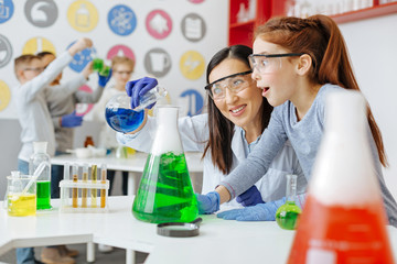 Wonders of chemistry. Charming chemistry teacher pouring blue chemical into a green one and smiling while her student being excited about the reaction