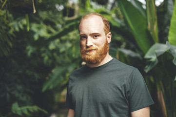 Portrait of confident young red headed man in a tropical garden surrounded by palm trees