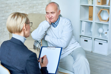 Portrait of bald senior man talking to female therapist during consultation, copy space