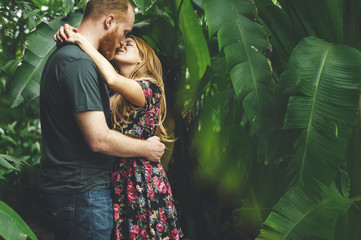 Young red headed couple kissing in a tropical grarden
