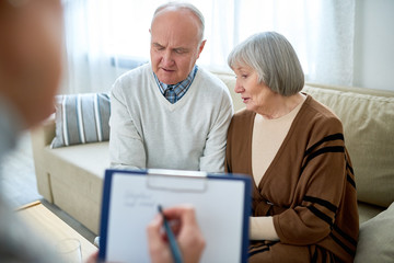 Portrait of nice senior couple visiting psychologist holding clipboard  sharing problems in therapy session