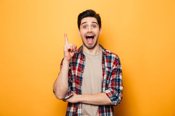 Portrait of a smiling young man pointing finger up
