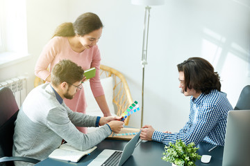 Content busy young designers viewing colors while thinking of product advertisement in modern office