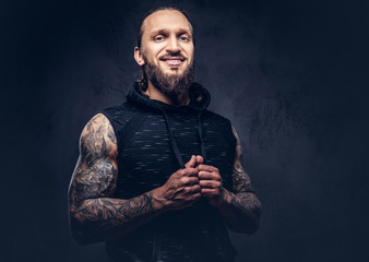 Portrait of a muscular bearded tattoed male with a stylish haircut wearing black sportswear, isolated on a dark background.