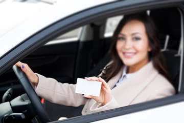 Portrait of smiling woman driver holding a white blank business card. Focus is on the white card