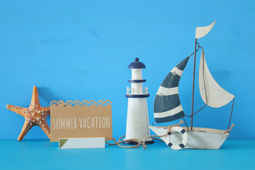 nautical concept image with sail boat, lighthouse, starfish and note over blue wooden table and background.