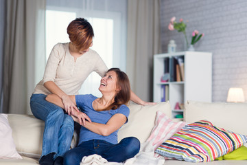 Homosexual couple of lesbian women at home on the couch hugging