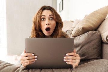 Image of excited european woman lying on sofa in living room, and expressing interest or surprise while using laptop