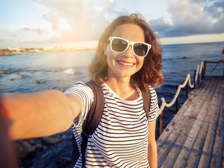 Beautiful young woman doing selfie on the sea and city background