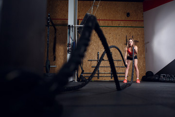 Portrait of sports woman in training with two ropes