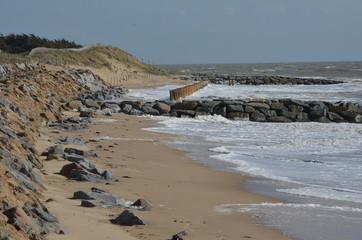 3 systèmes anti érosion : enrochement de la dune (à gauche) et pieux au milieu de 2 épis rocheux
