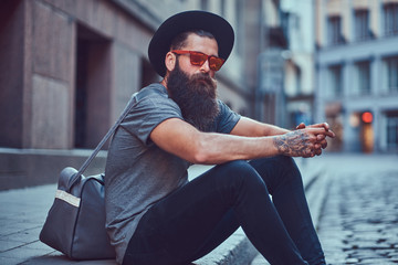A handsome hipster traveler with a stylish beard and tattoo on his arms dressed in casual clothes with a bag, sits on the sidewalk, resting after a bike ride.