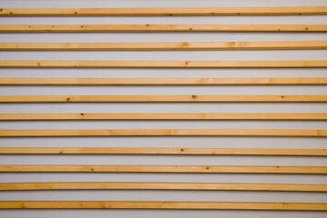 Wooden horizontal slats batten on a light gray wall background. Interior detail, texture, background. The concept of minimalism and Scandinavian style in the interior. Copy space