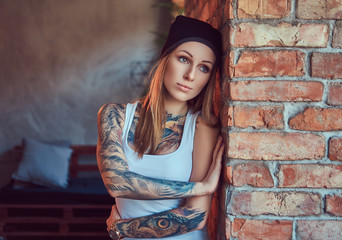 A tattoed sexy blonde in a t-shirt and a hat posing against a brick wall.