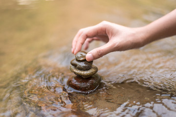 Close up hand to doing Stone stacked in water river